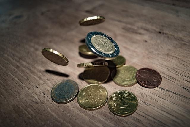 pár mincí se sype seshora na stůl, některé už leží na stole