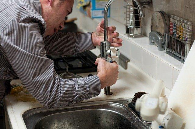 muž opravuje kohoutek